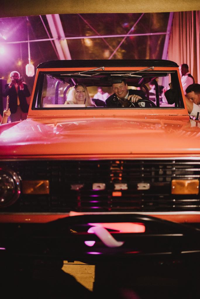 bride and groom riding in orange bronco getaway car