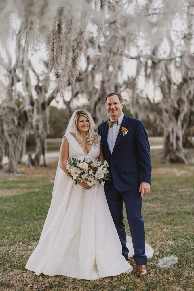 bride and groom posing beneath spanish moss