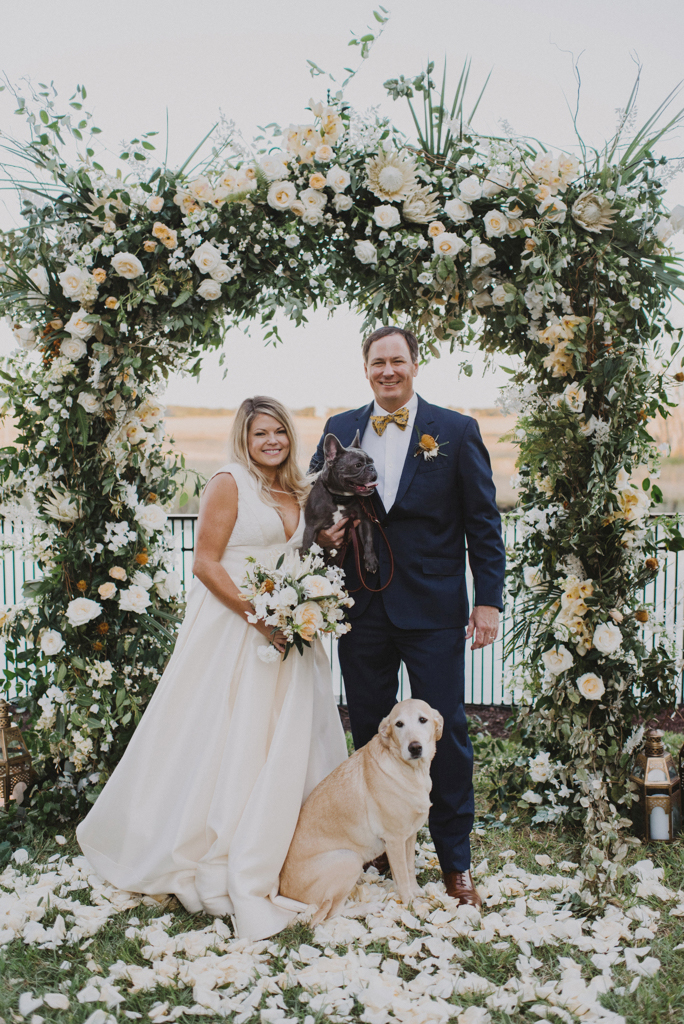 bride and groom posing with their dogs beneath floral arch
