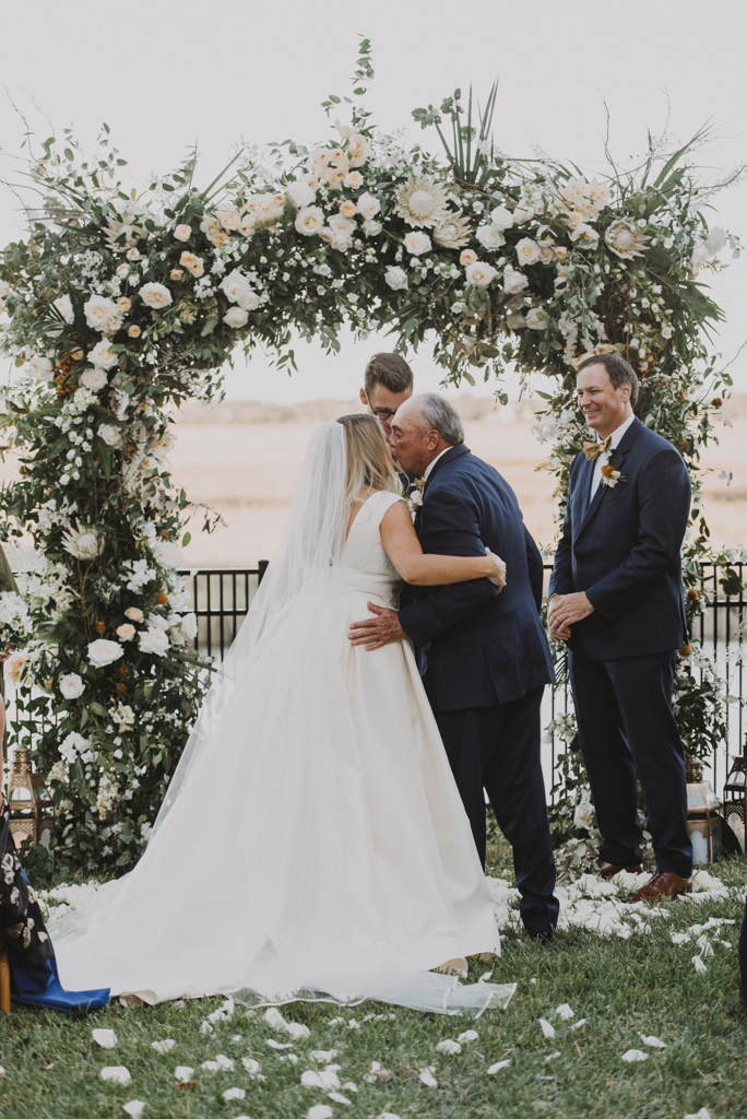 father giving away the bride beneath floral arch