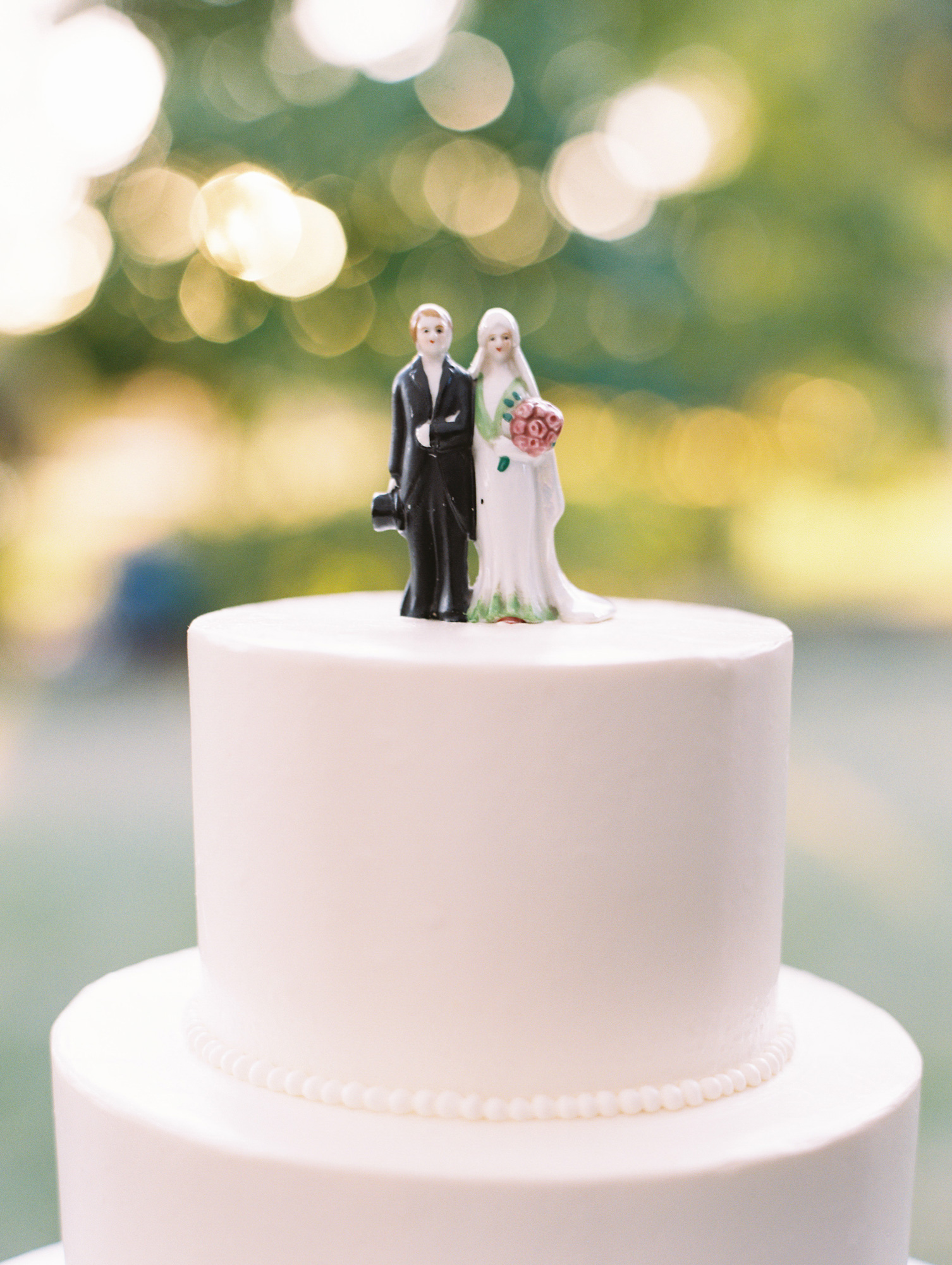 top tier of white wedding cake bride and groom topper