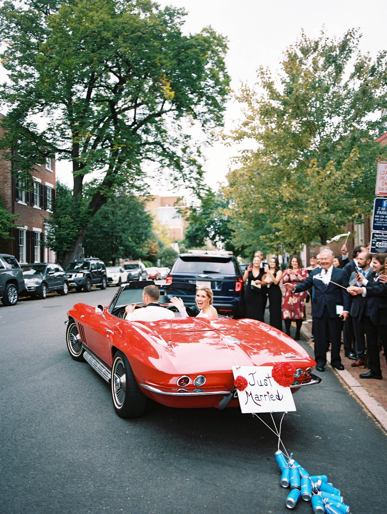 bride and groom driving away in just married car