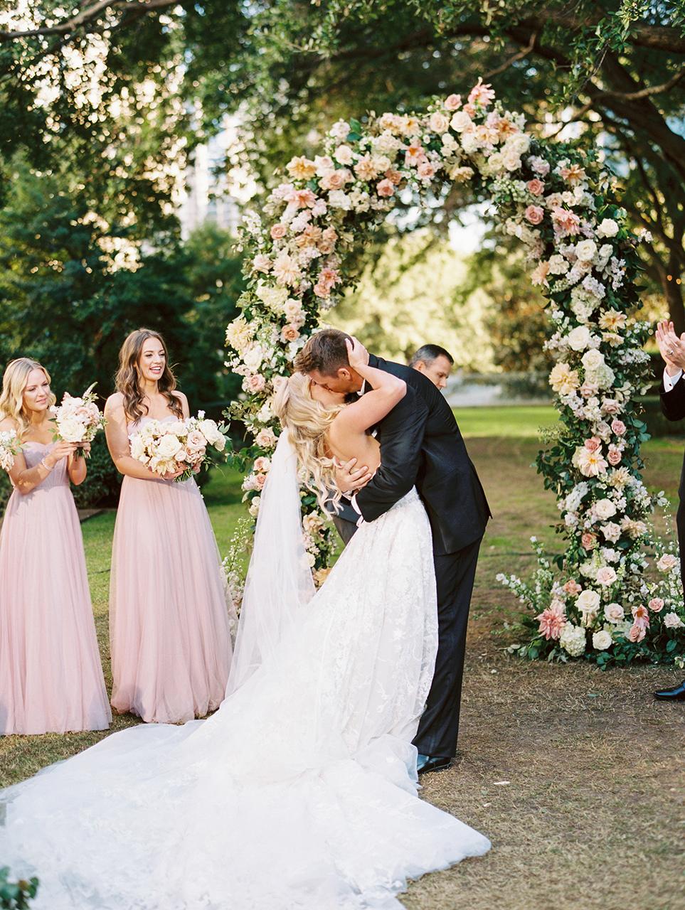 floral arch wedding ceremony bride groom kiss