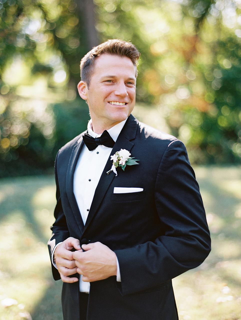 groom posing in black tuxedo outdoors