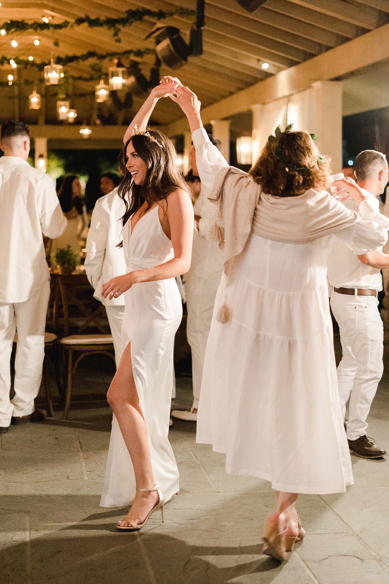 bride in white dancing at rehearsal dinner with guests