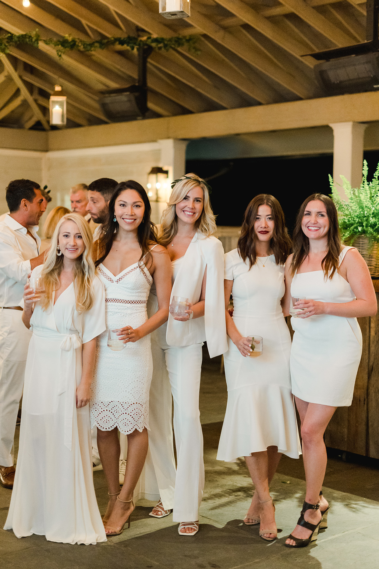 guests dressed in white posing with drinks at rehearsal dinner