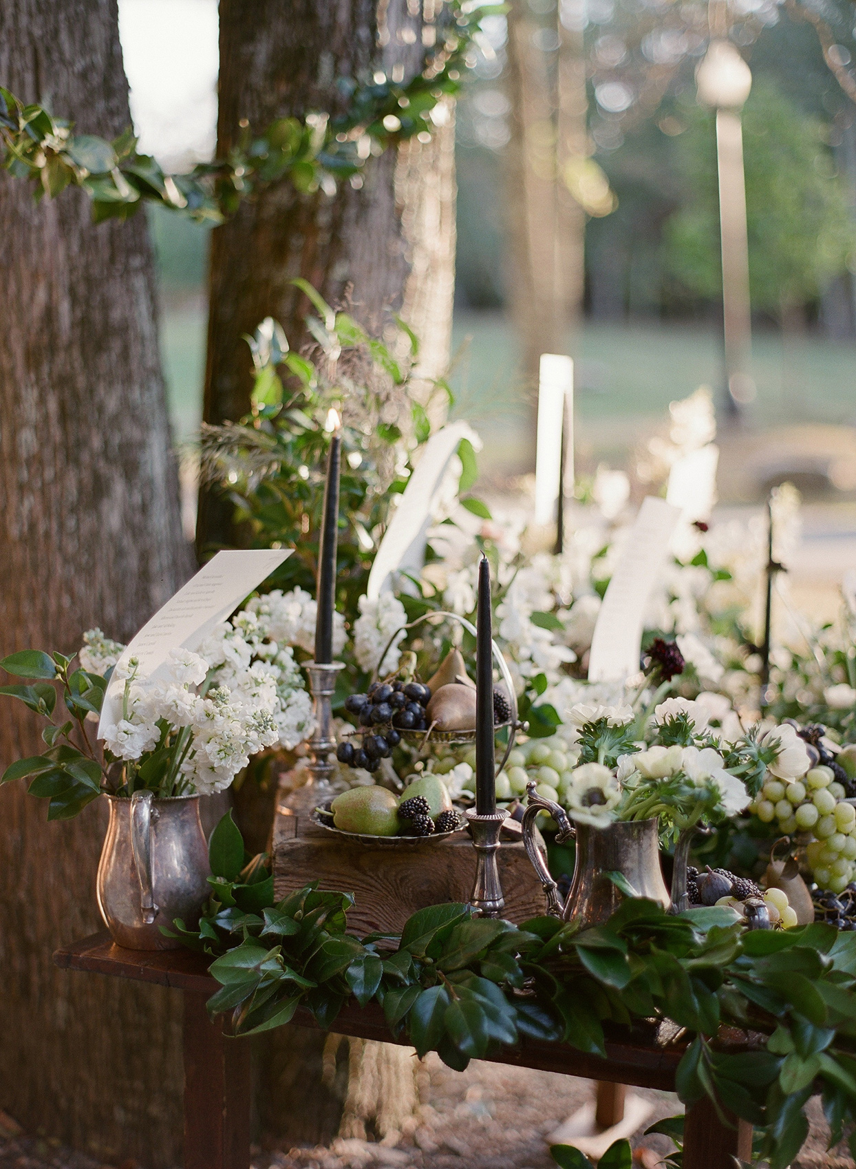 ornate metal jugs filled with flowers and seating chart papers at rustic table