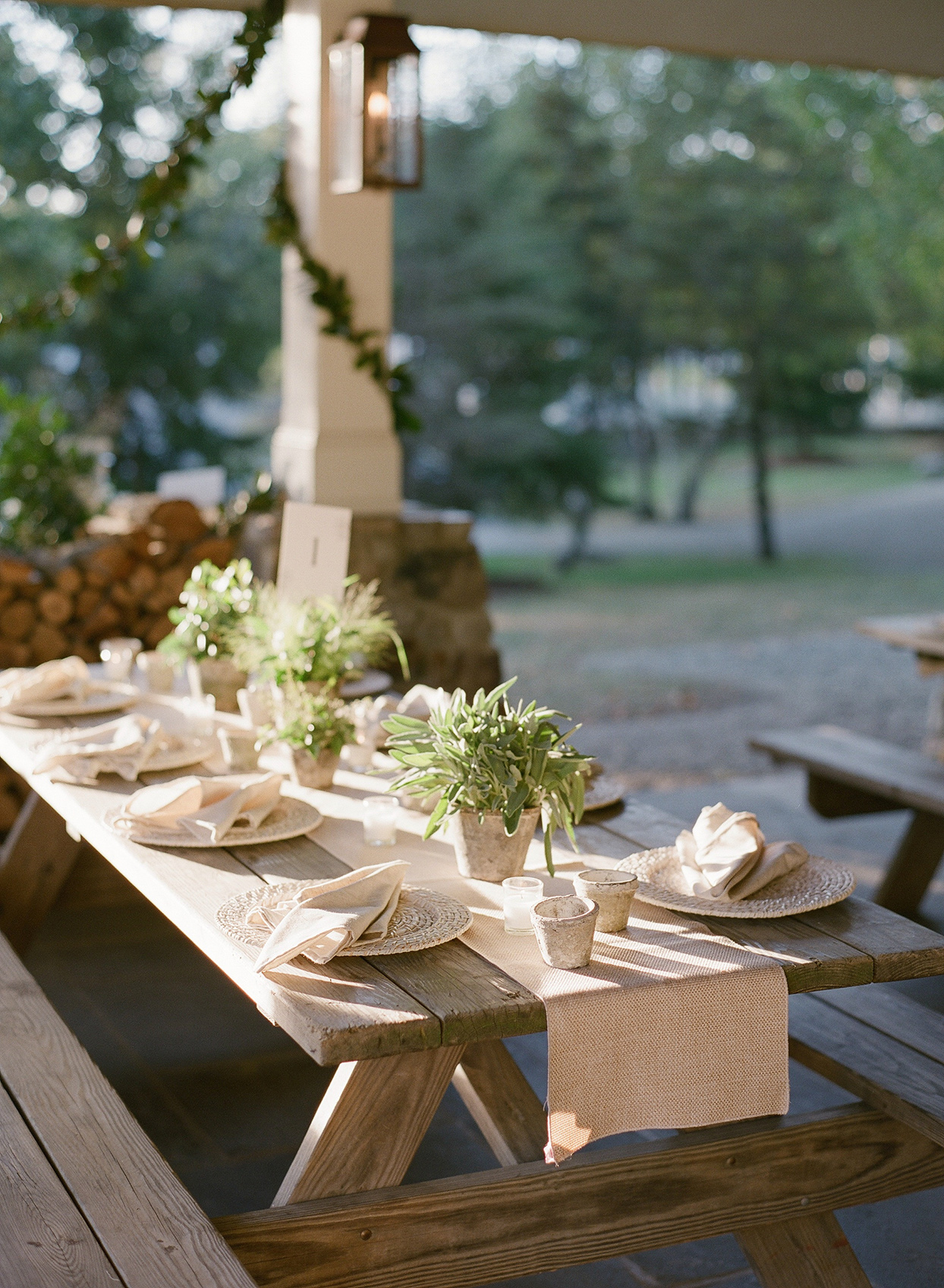 picnic dinner tables set with neutral tones and plant centerpieces for rehearsal dinner