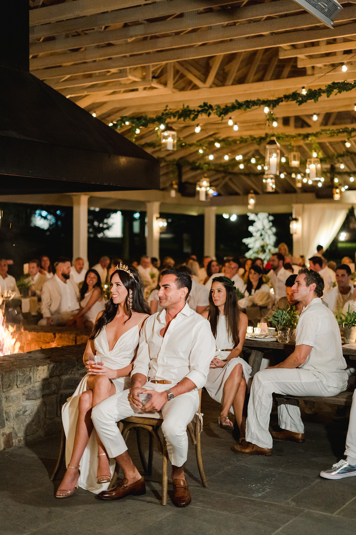 bride and groom and guests in white during rehearsal dinner toasts