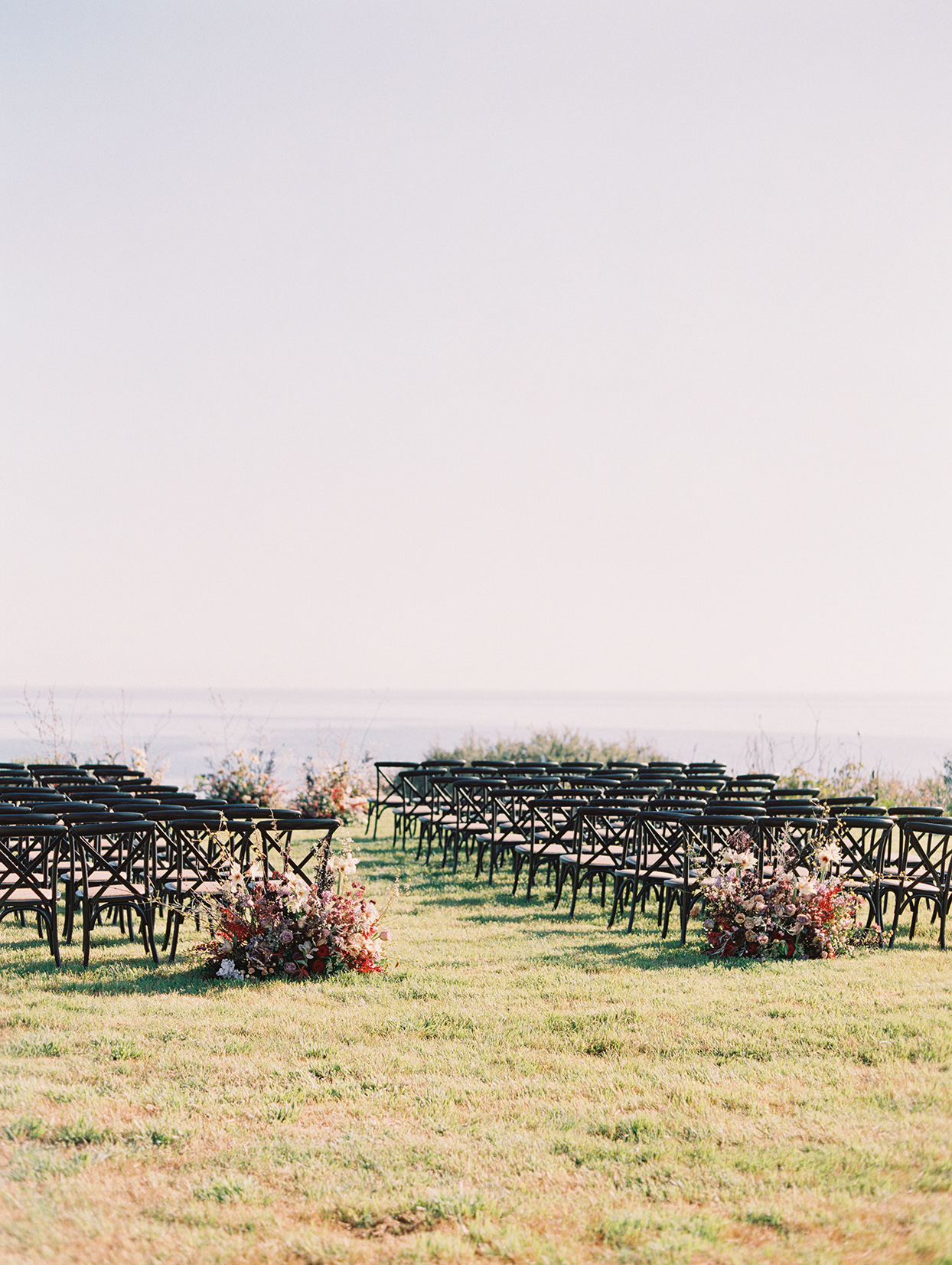 wedding ceremony space with black chairs set up on grass by ocean