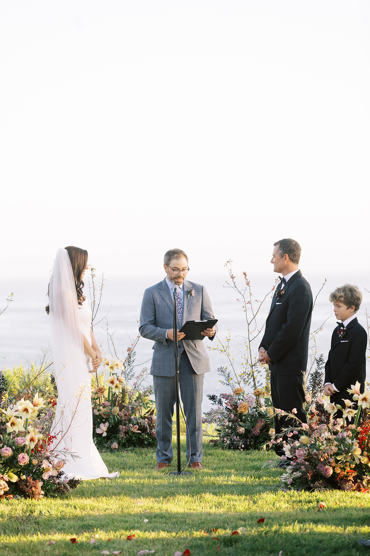 wedding ceremony couple and officiant amidst flowers