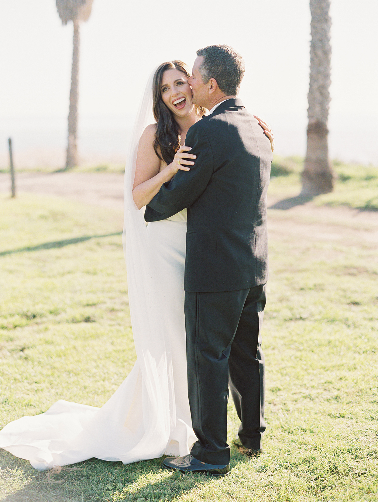 couple hugging during first look on lawn