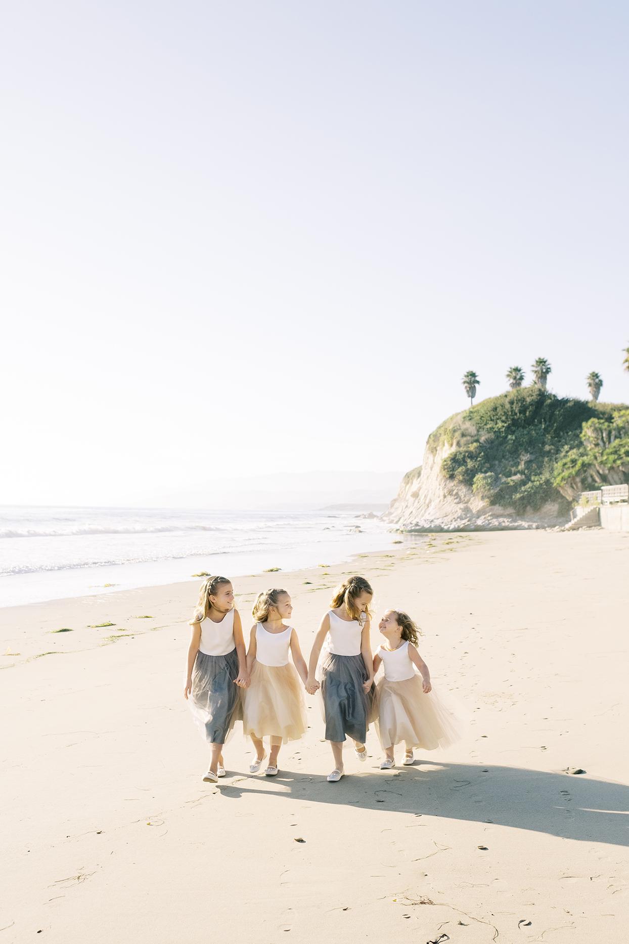 flower girls walking hand in hand on beach