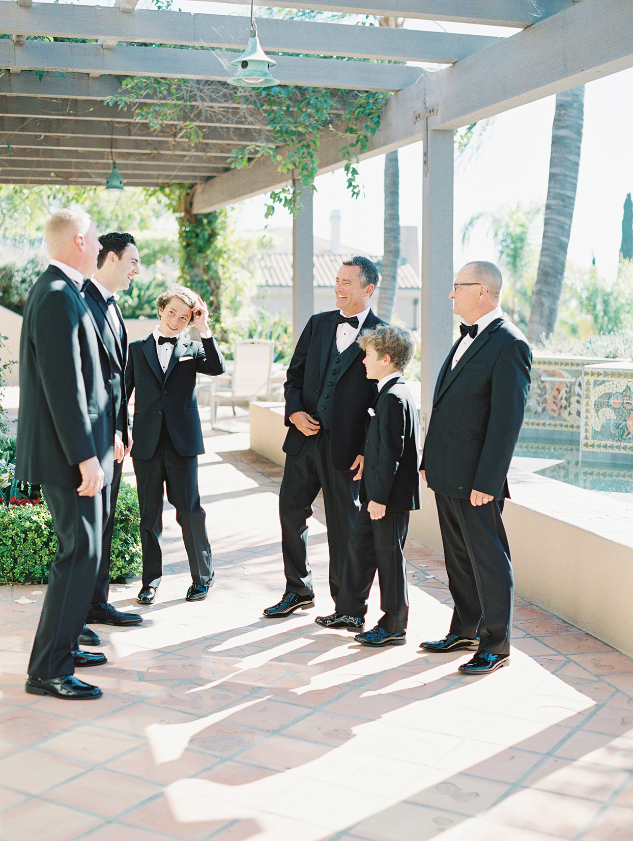 wedding men in black suits standing on patio
