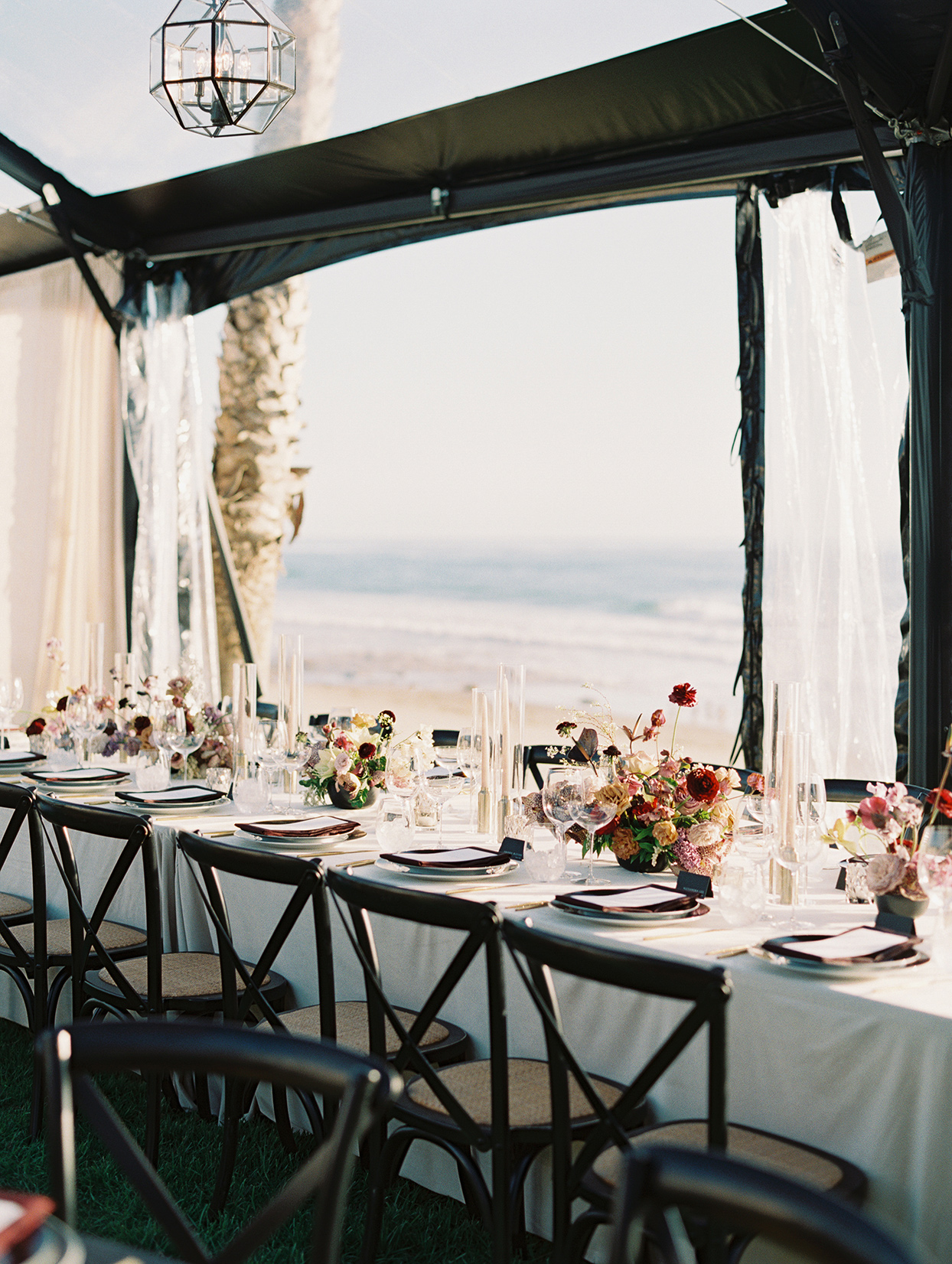 long reception table with black chairs overlooking beach