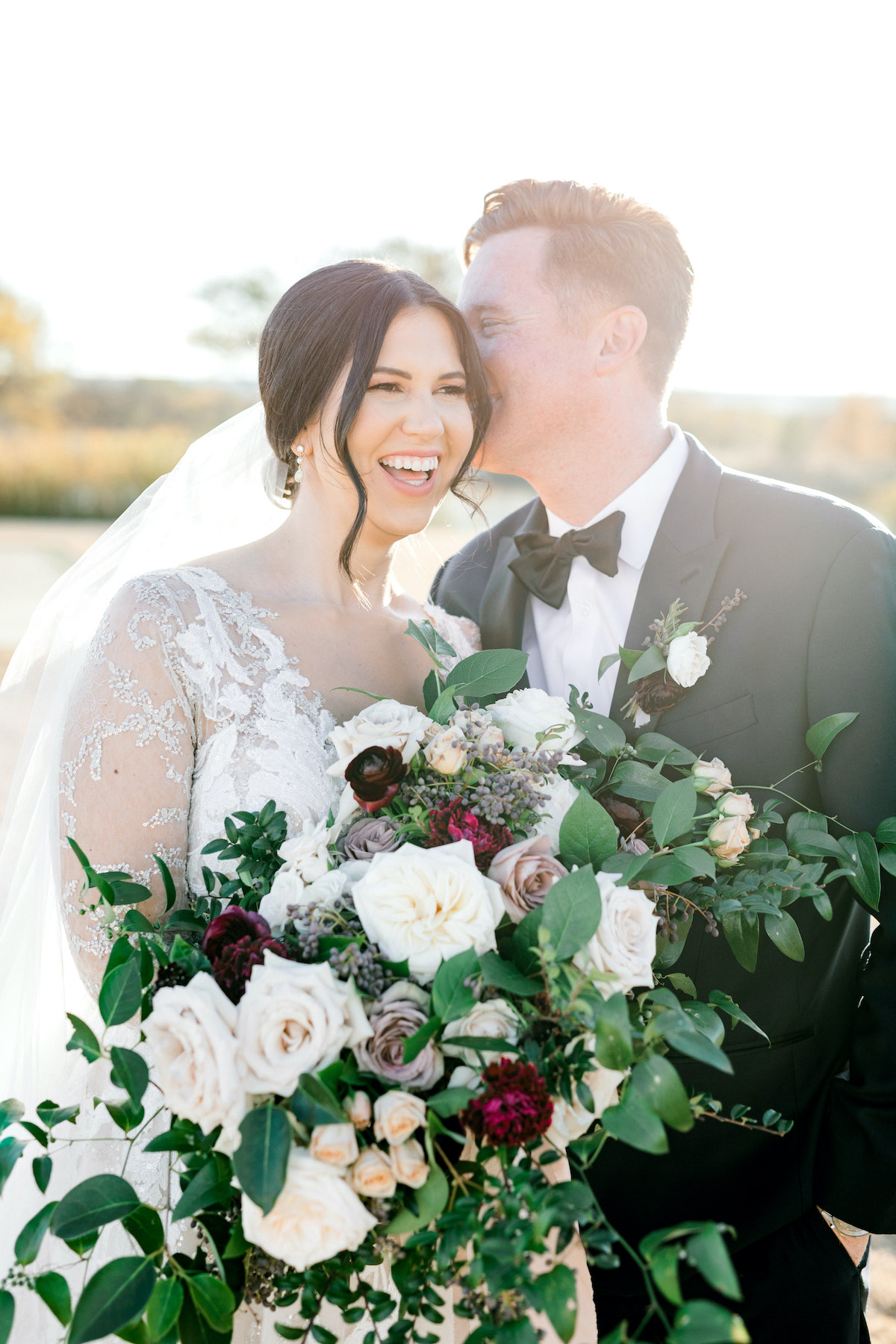 bride and groom with floral white and purple wedding bouquet