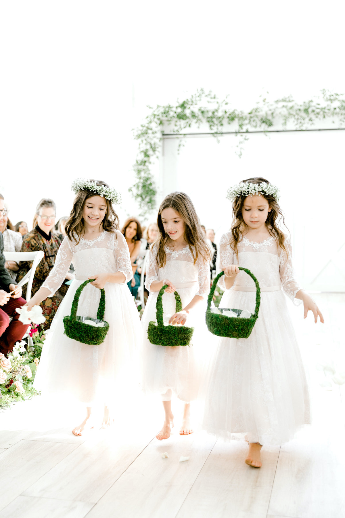 flower girls in white with grass baskets walking down aisle