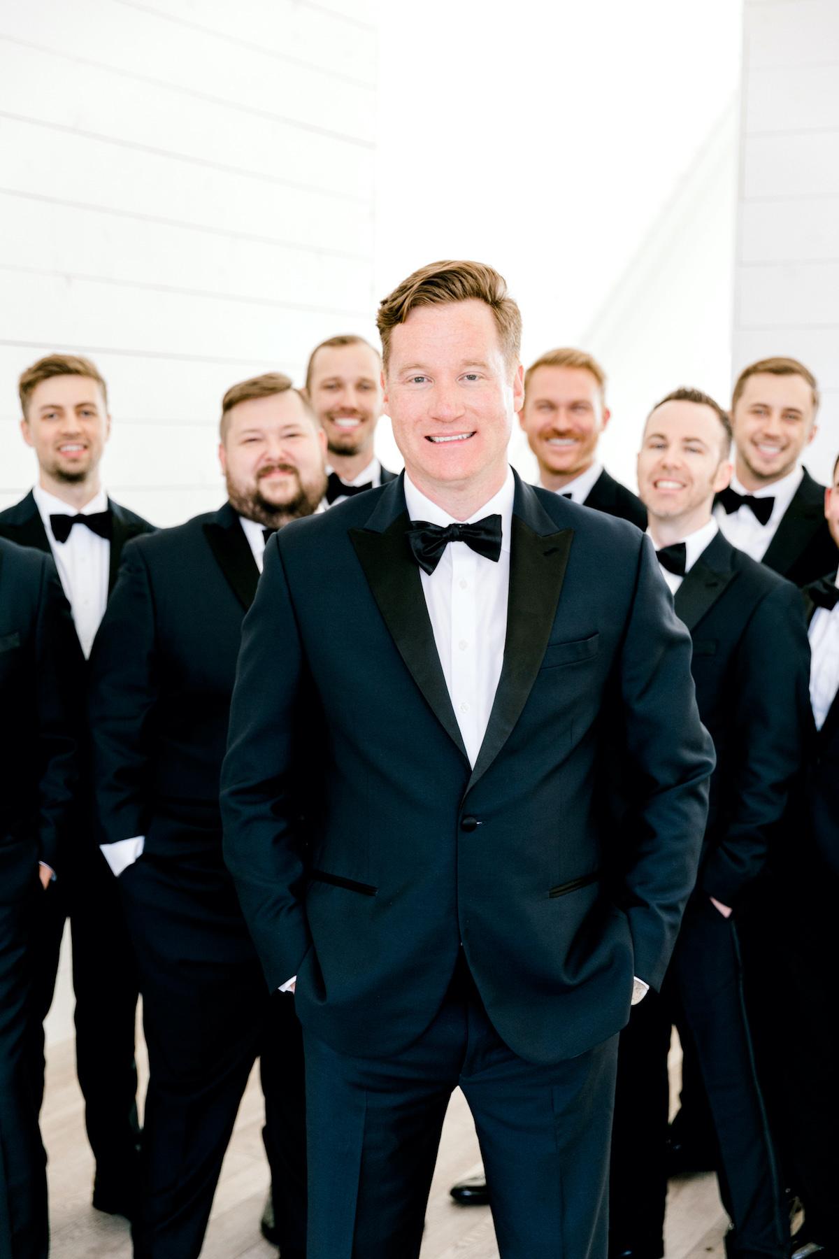 groom in navy with groomsmen standing behind him