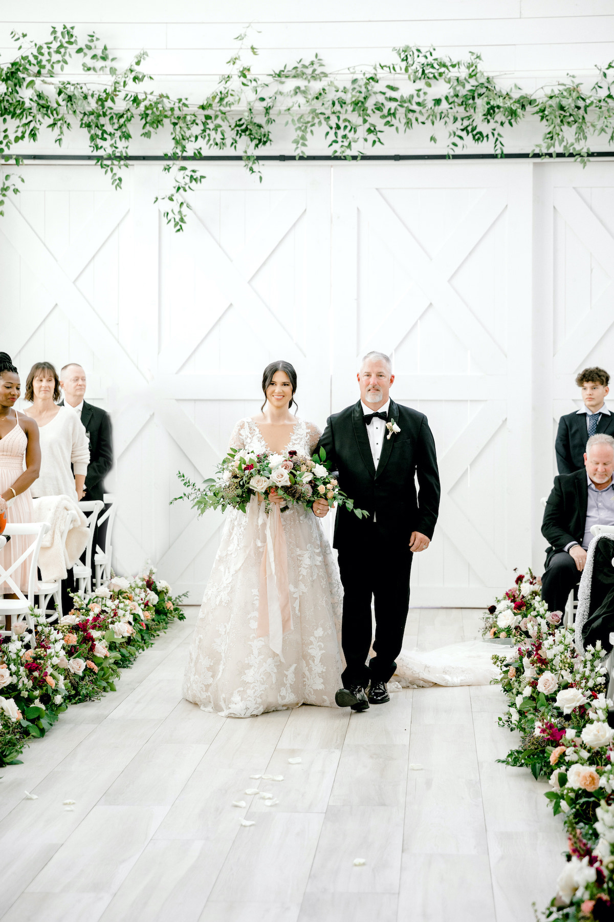 bride and father processing down white barn aisle lined with flowers