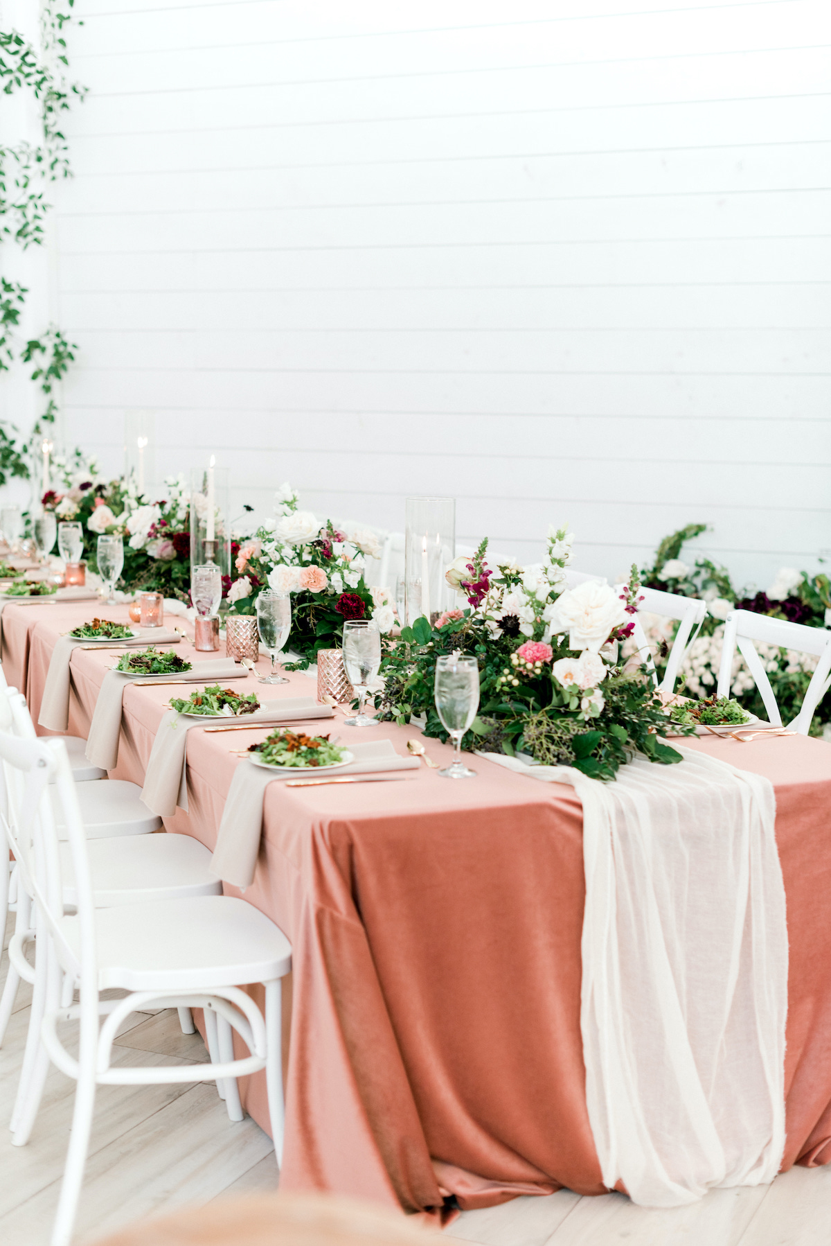 long reception tables with coral clothes and greenery centerpieces