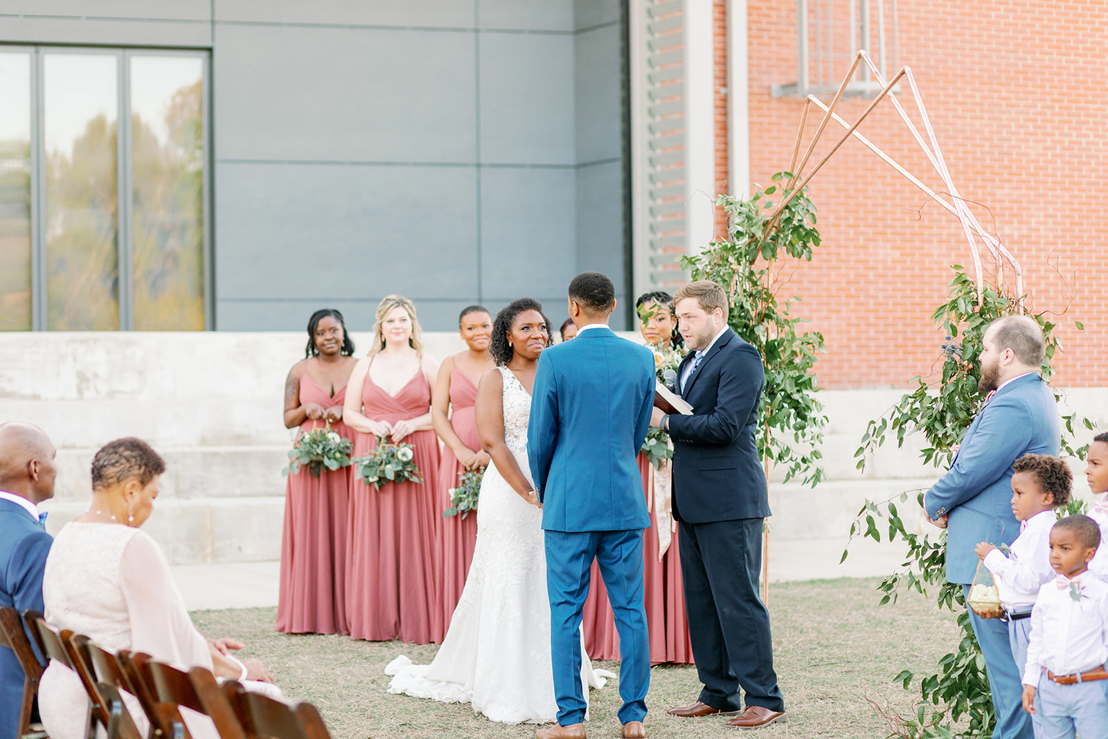 bride and groom holding hands during ceremony while wedding party looks on