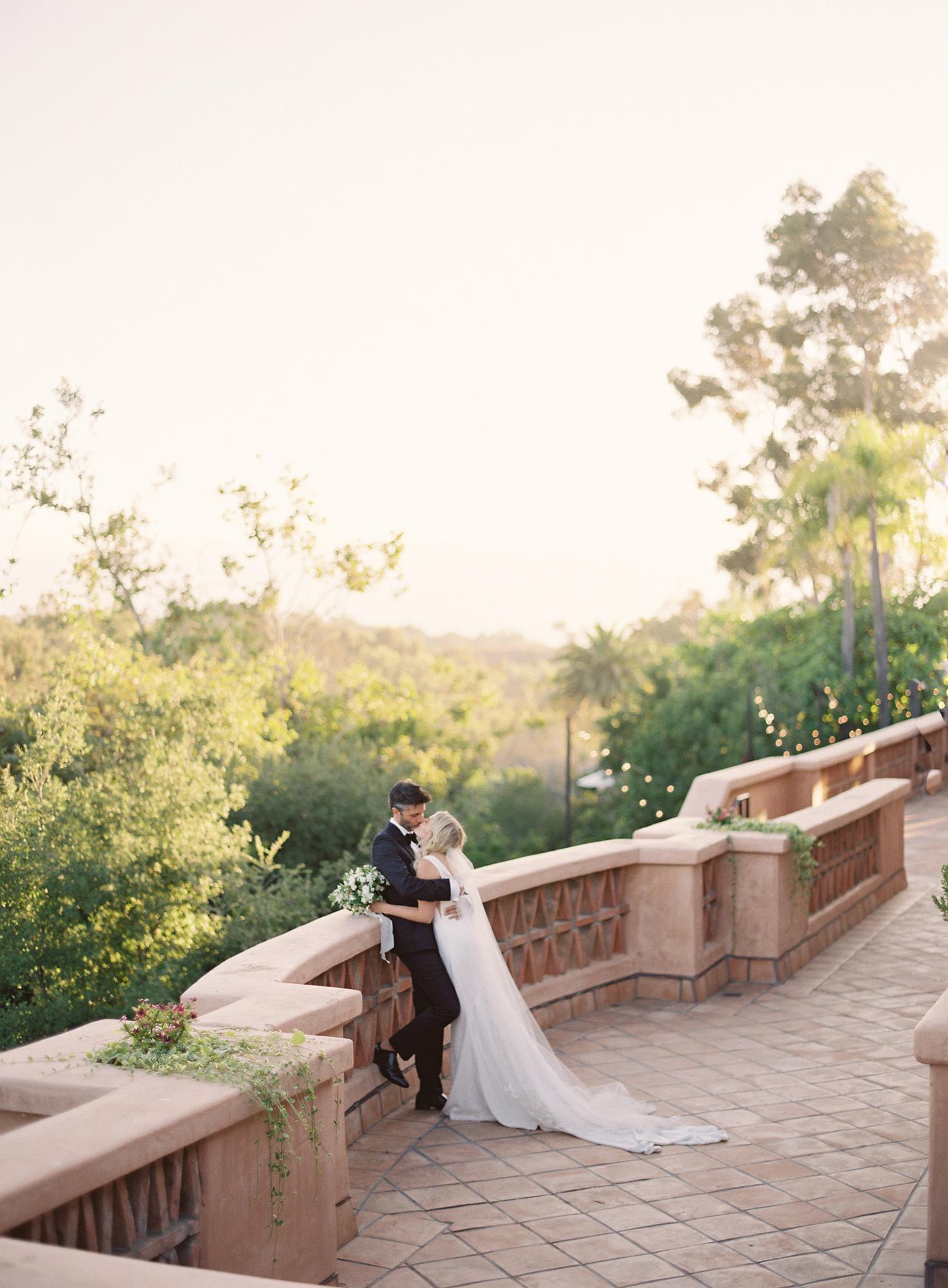 wedding couple kissing on balcony