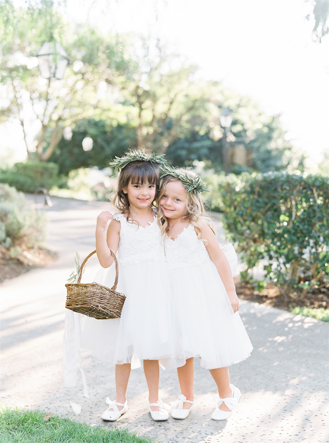 Flower girls in white dresses with tulle skirts and lace accents, paired with bow-tied flats