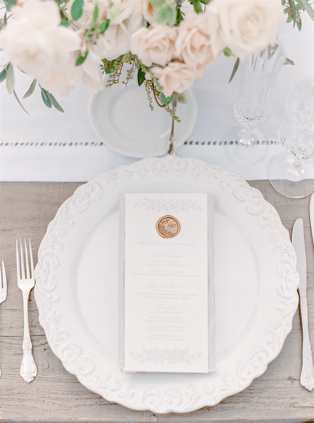 Place setting with white ceramic chargers with a vintage-inspired textured border, silver flatware, and crystal stemware
