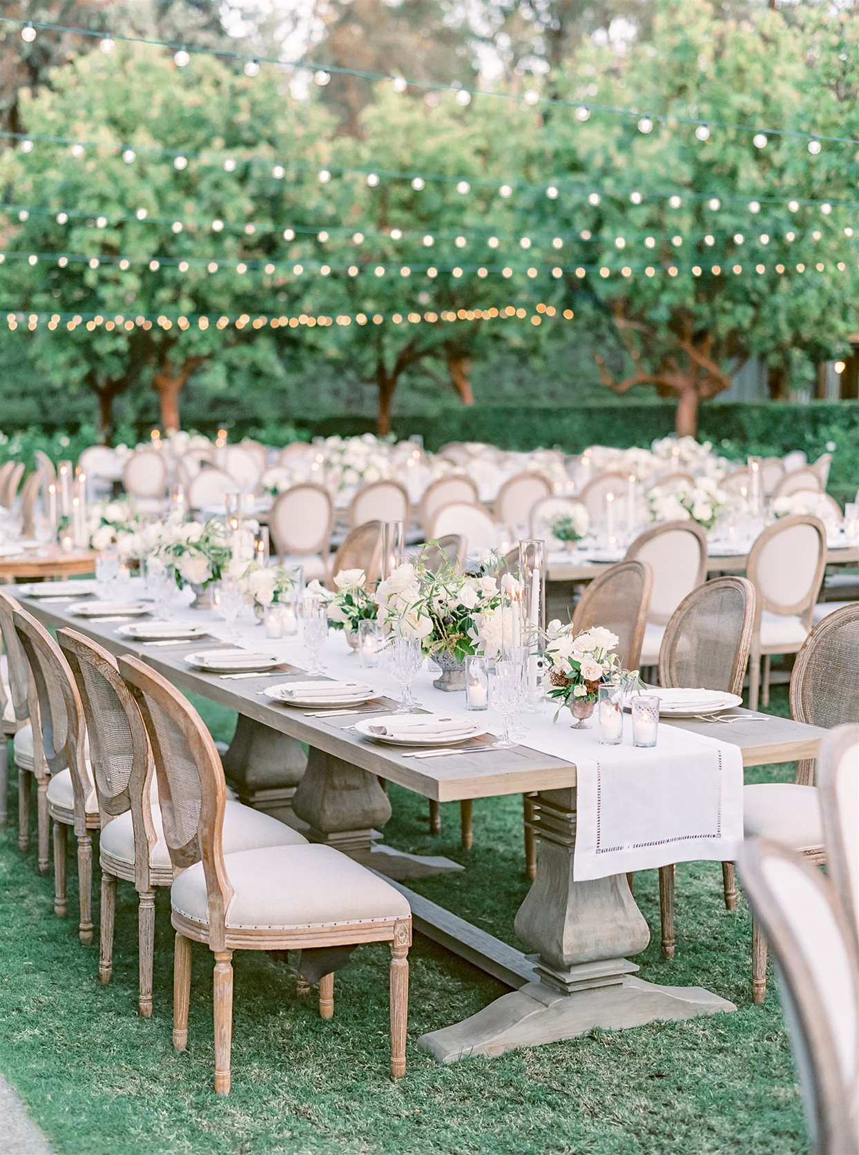 Outdoor reception with light wood tables and upholstered chairs and ivory runners