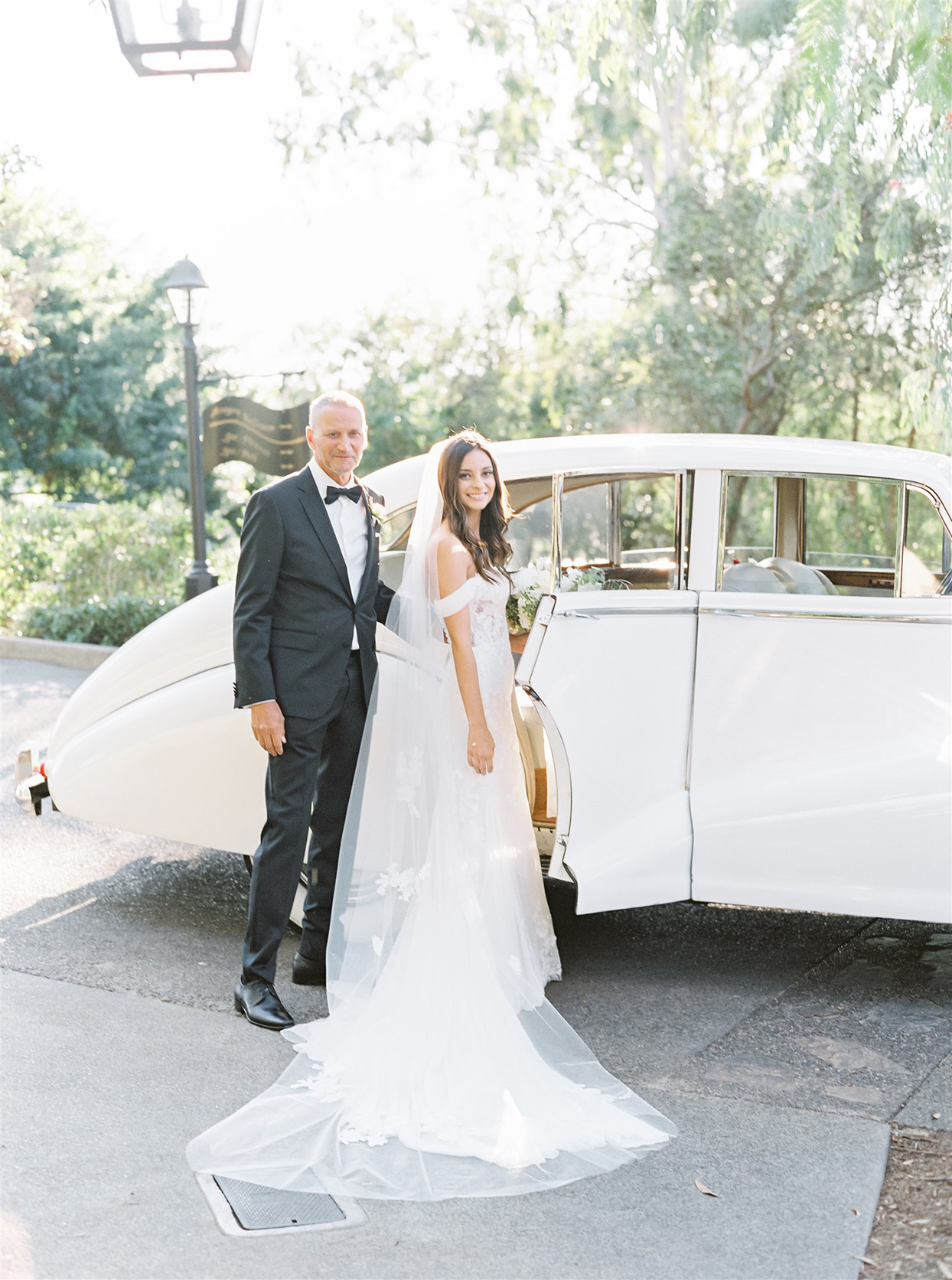 Bride and father next to vintage car