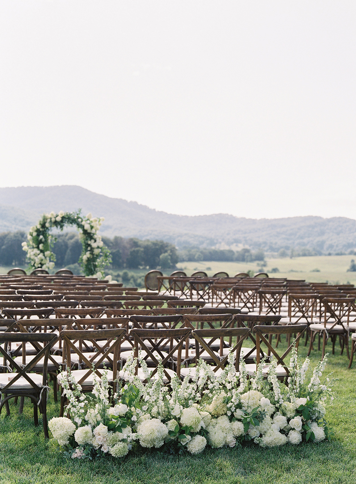 elegant outdoor farm ceremony with wooden chairs and white flower decor