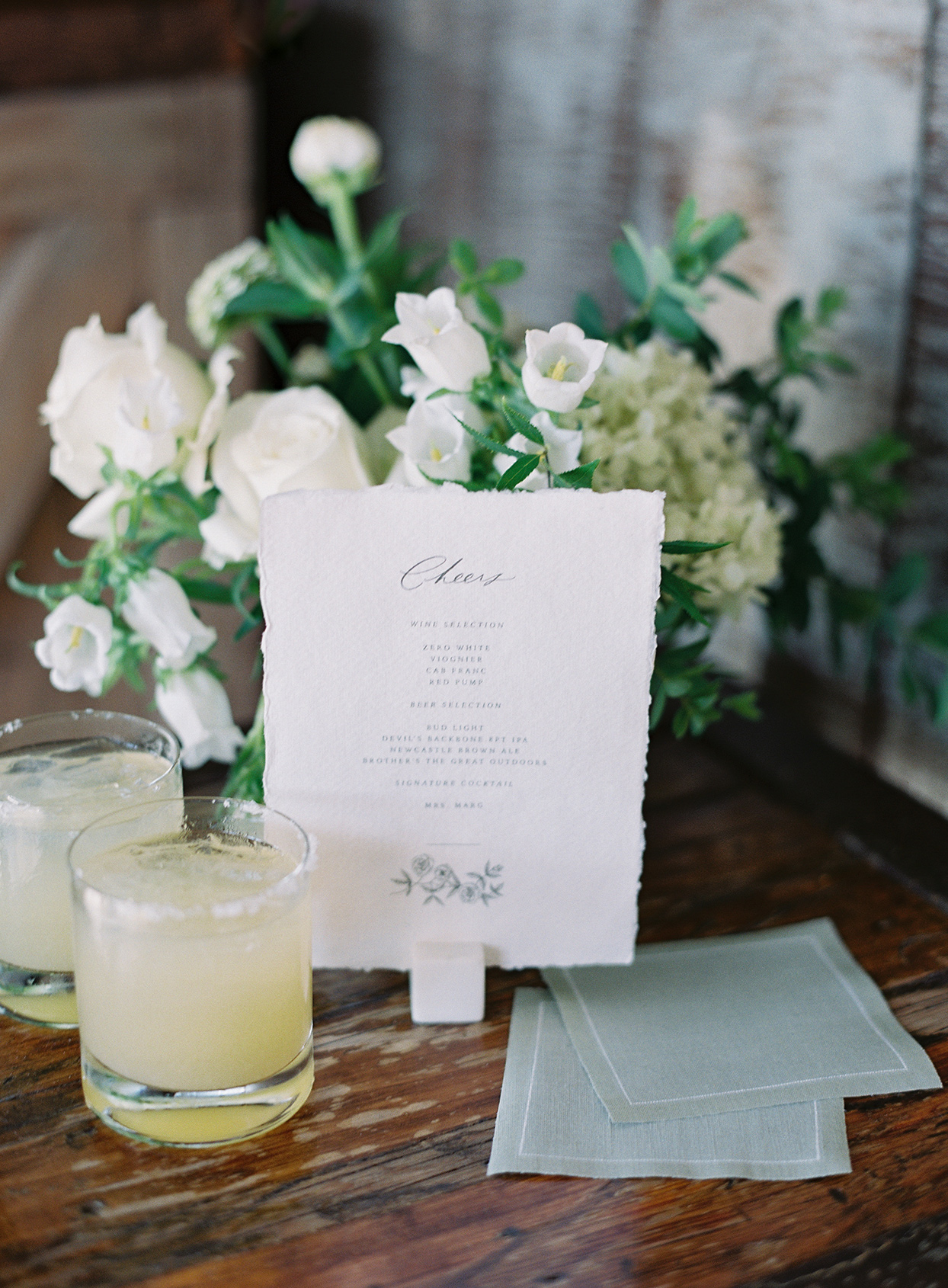 wedding cocktails next to sign and flowers