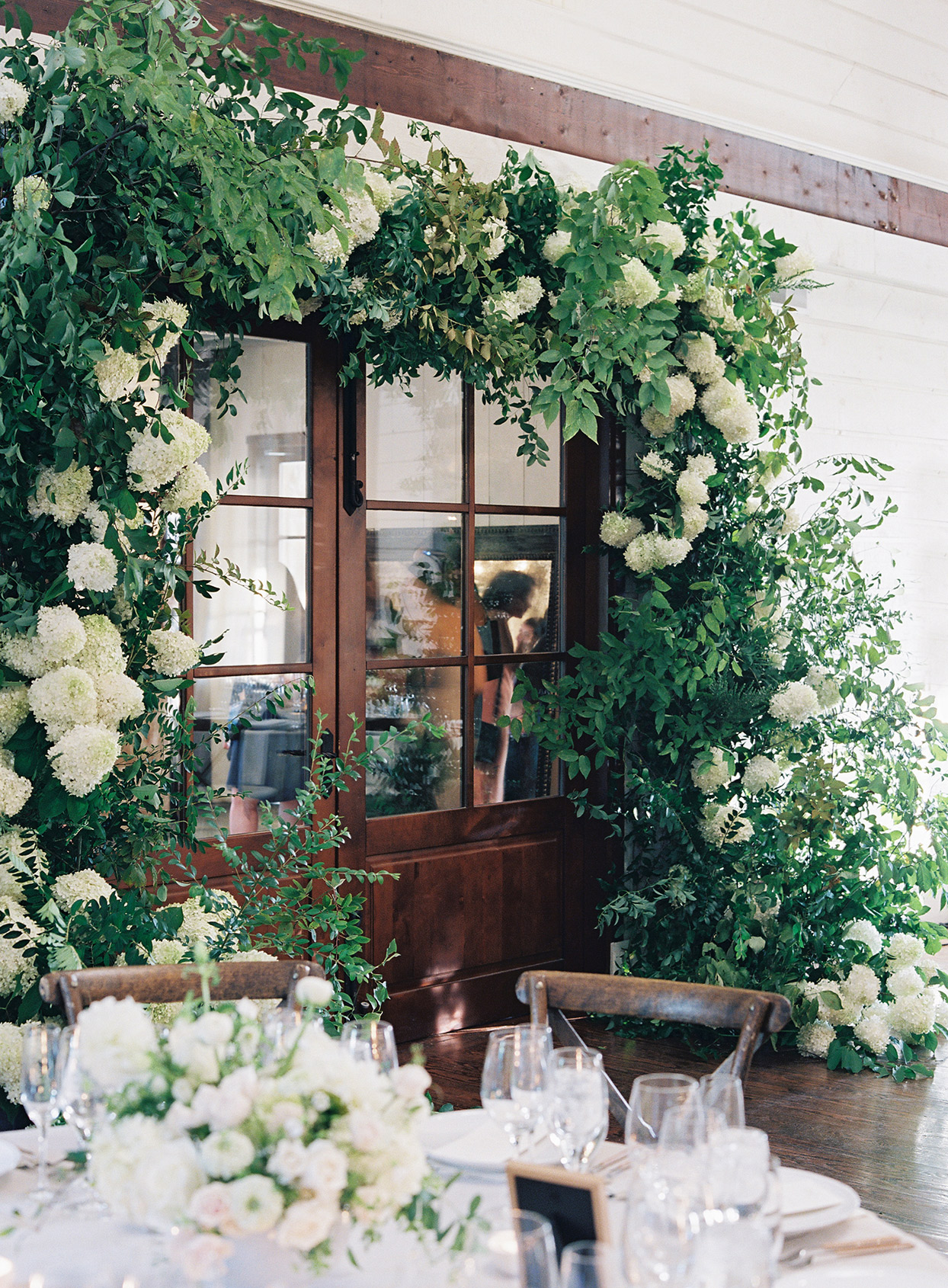 wedding reception large floral arch over french doors