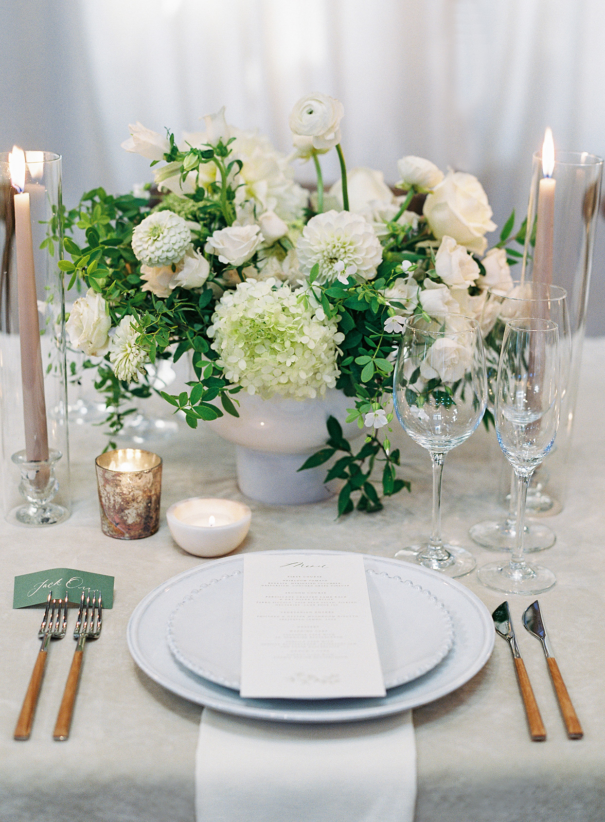 elegant white and green place setting with floral bouquet centerpiece