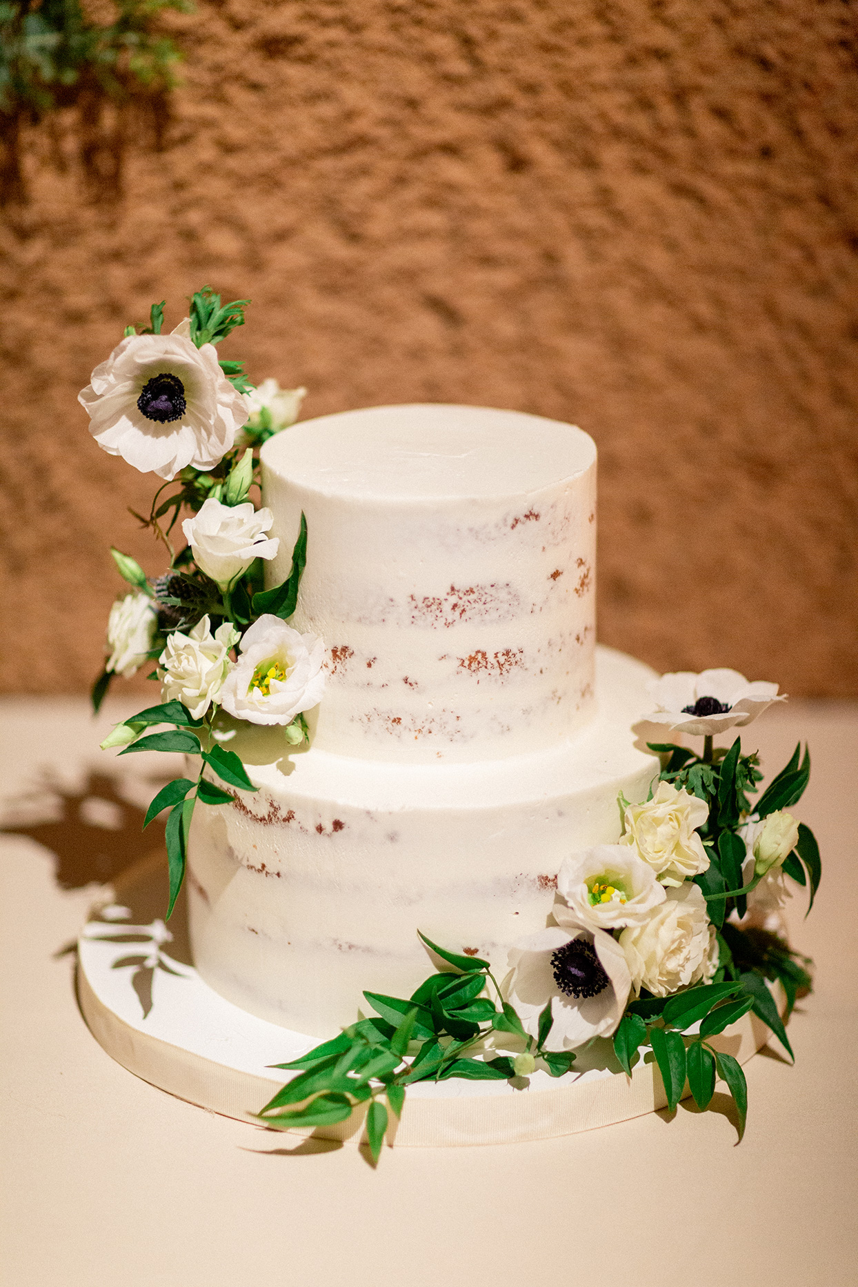 simple almost naked wedding cake with white flowers