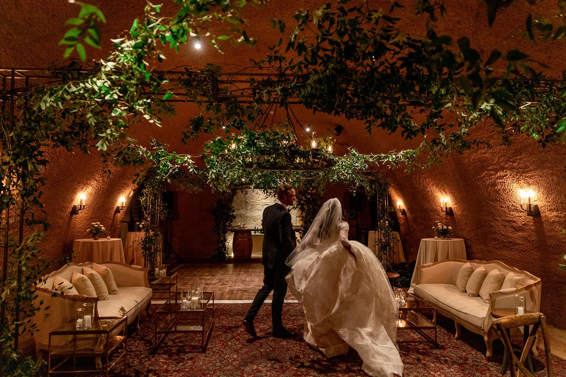 bride and groom walking through wedding cave