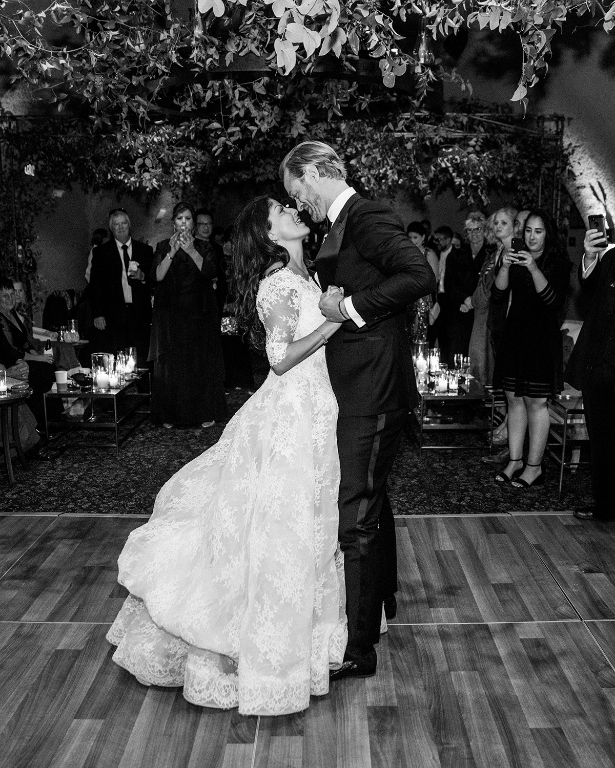 wedding couple first dance under greenery decorations