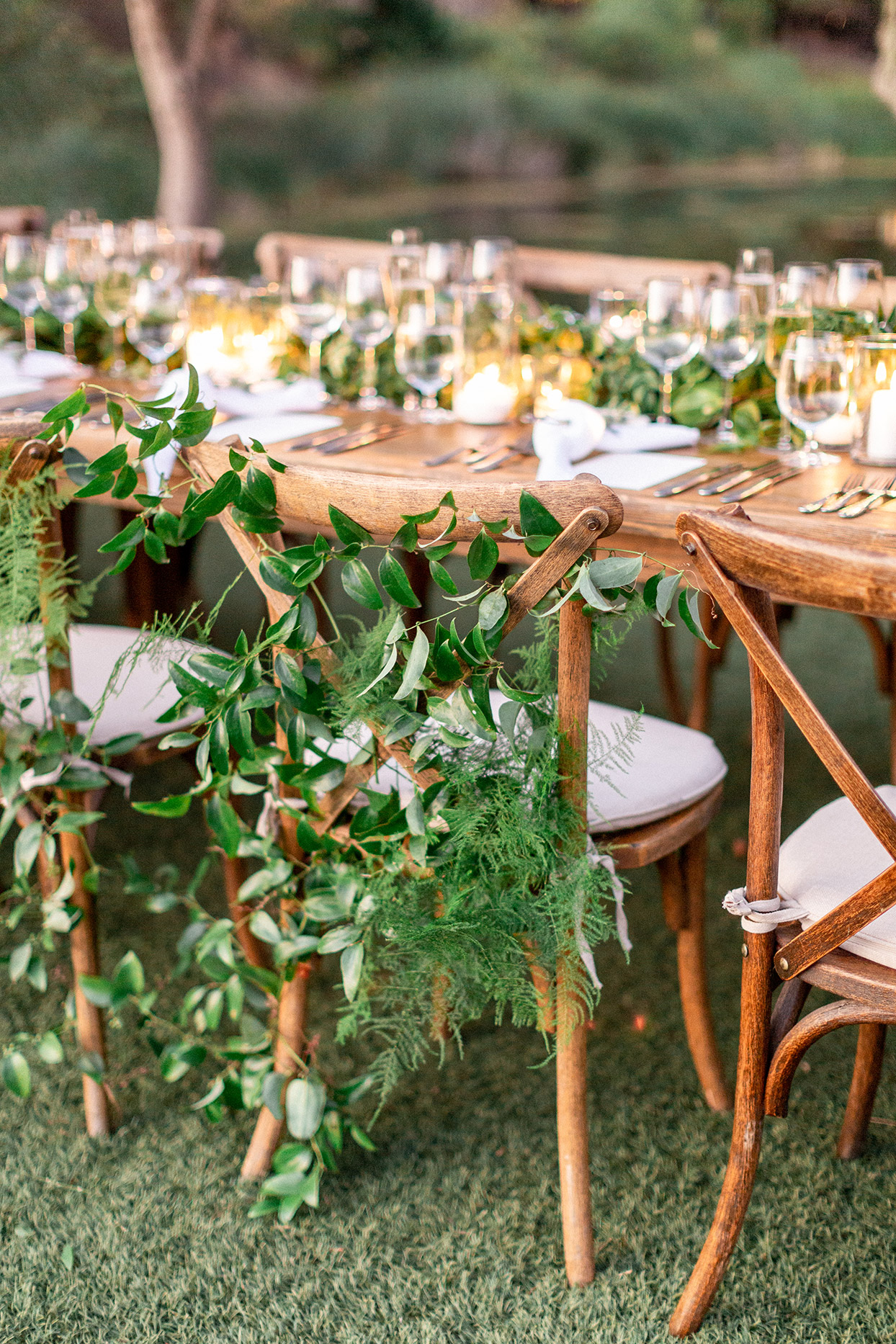 wedding reception wooden chairs with greenery decor