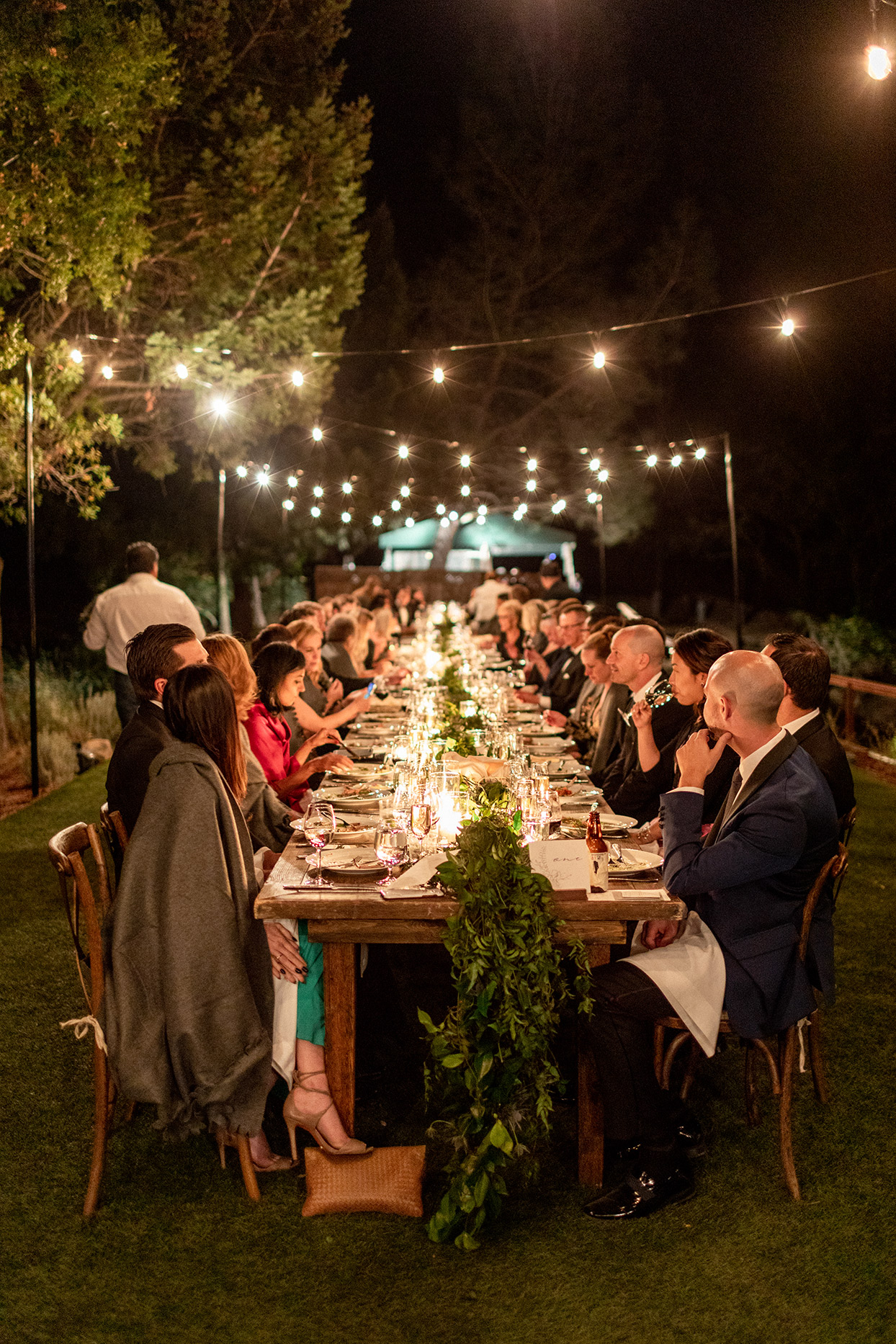 guests eating at evening reception elegant long table under string lights