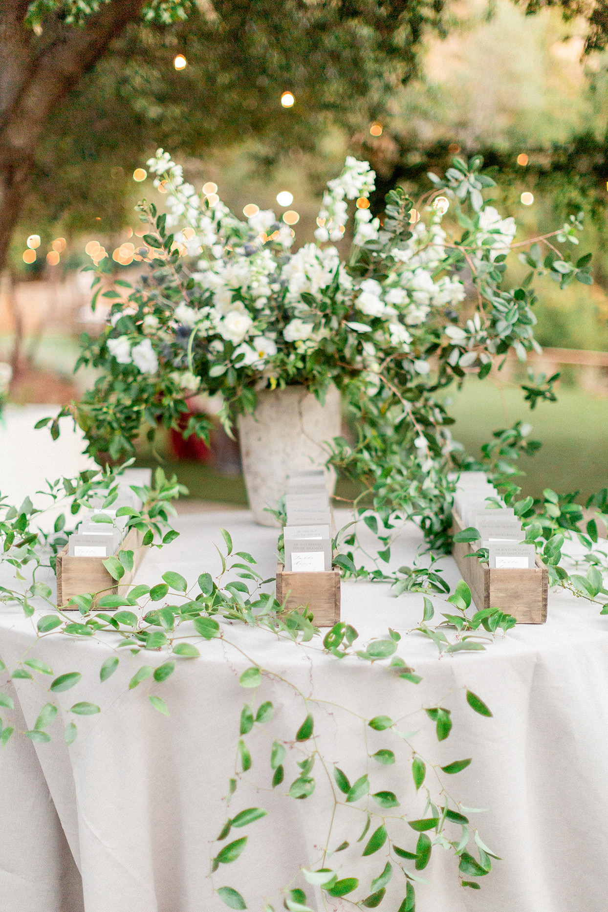 neutral tones wedding seating cards in wooden boxes on white table