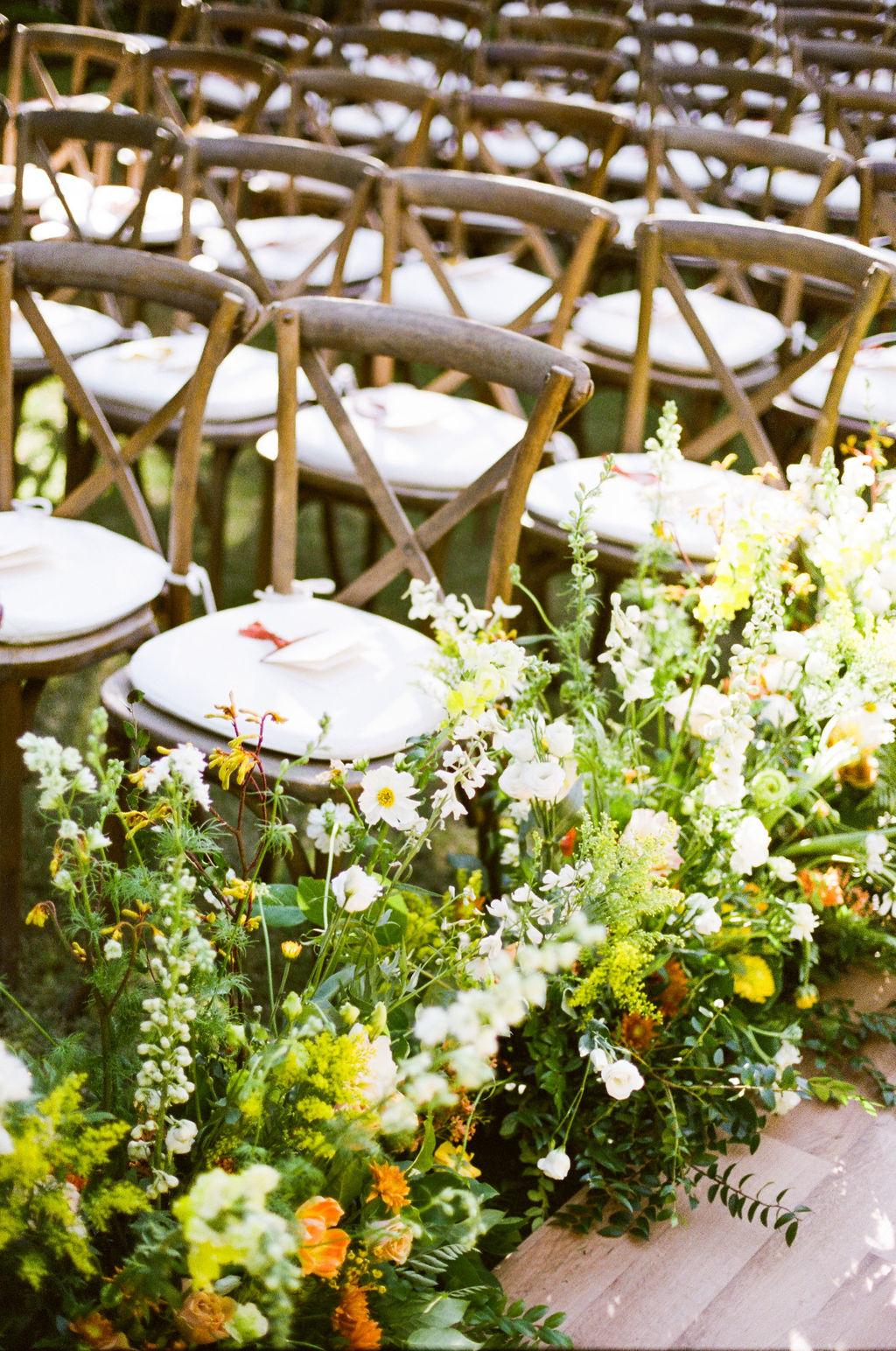 floral arrangements lining ceremony aisle