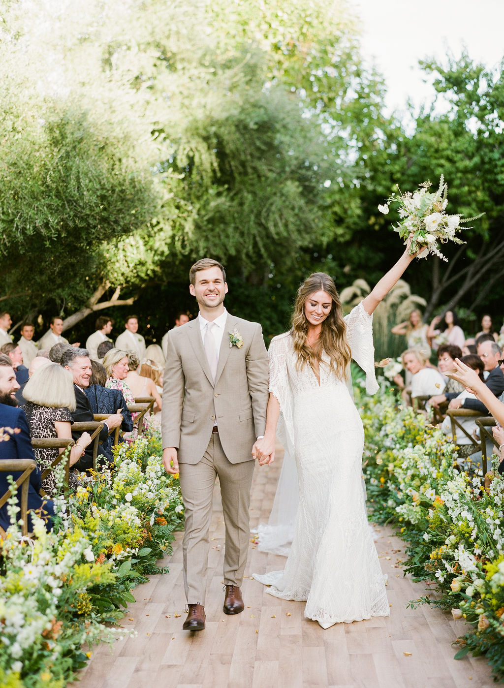 bride and groom holding hands recessing down aisle lined with flowers