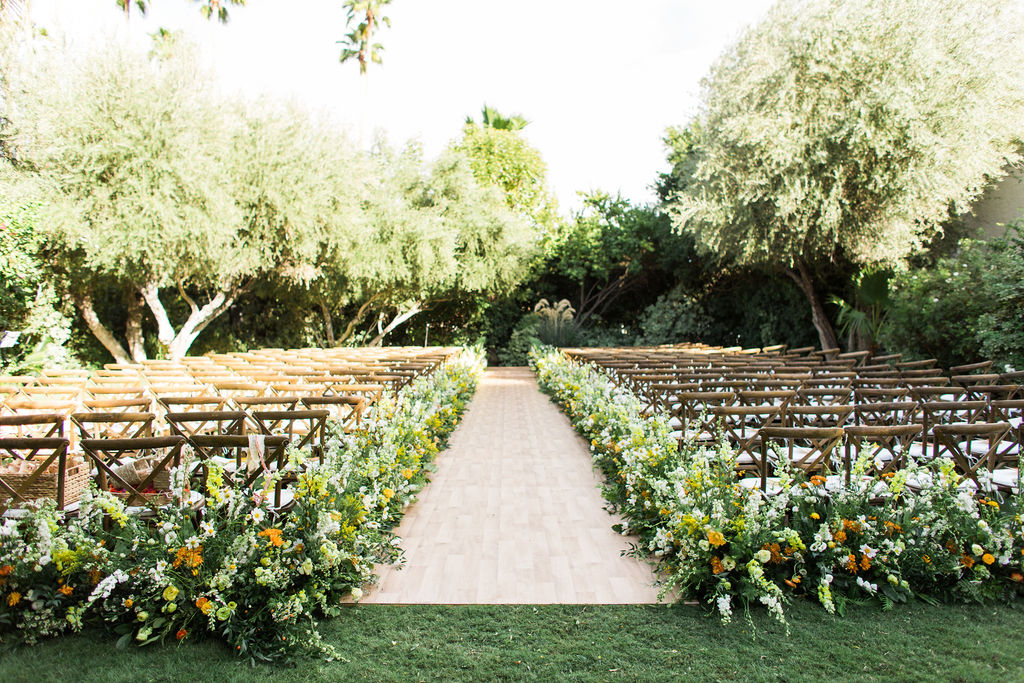 wedding ceremony outdoor space set up with chairs and tree backdrop