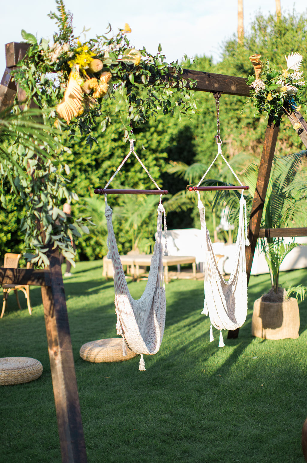 hammock swings hanging from rustic wooden beam with flowers for wedding cocktail hour