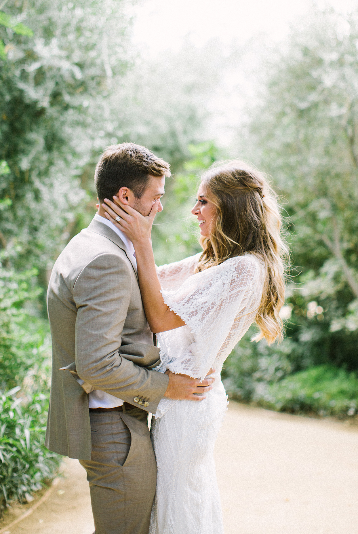 bride and groom embracing during first look on garden path