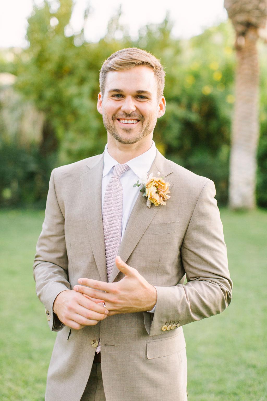 groom in light brown suit with pastel pink tie