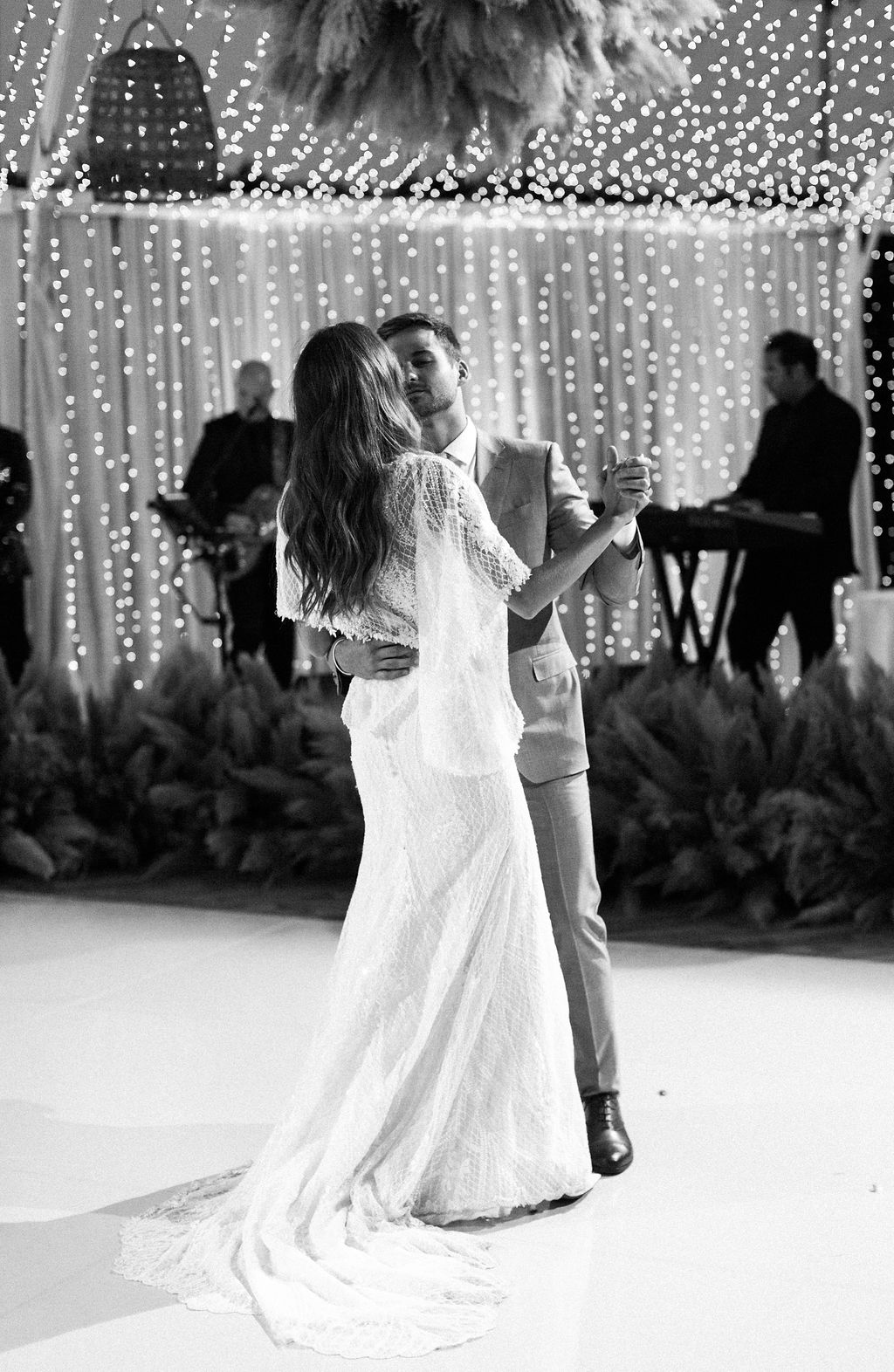 bride and groom sharing first dance with twinkling light backdrop