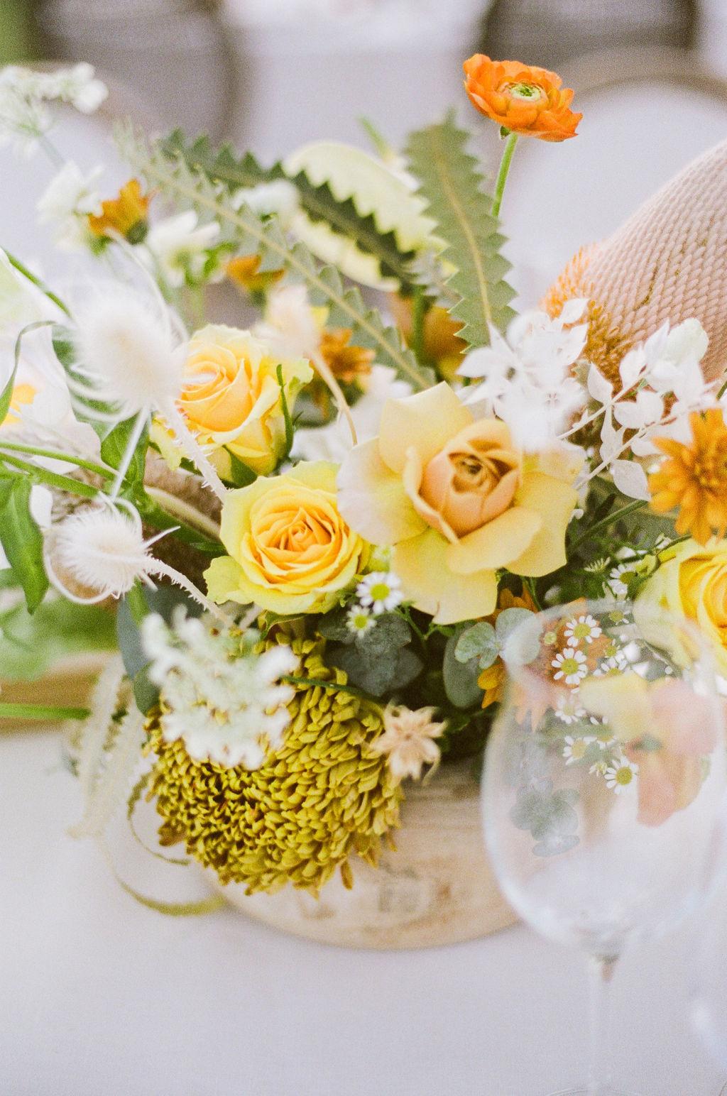 citrus colored floral bouquets at wedding reception
