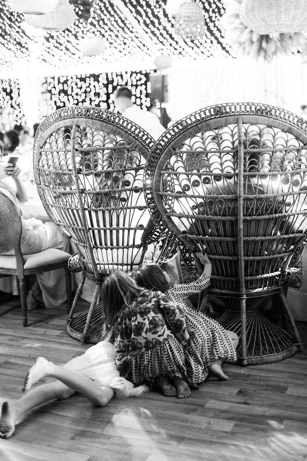 kids peeking around large wicker chairs at wedding reception