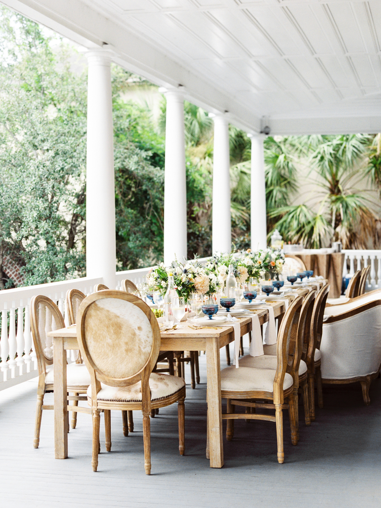 long wedding brunch table set up on large white porch
